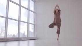 Den attraktiva yogakvinnan som öva balansera yoga, poserar lager videofilmer