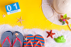 Den Augusti 1st bilden av den august 1 kalendern med sommarstrandtillbehör och handelsresanden utrustar på bakgrund för sommarter Royaltyfri Bild