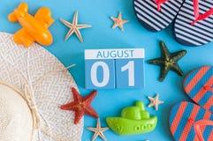 Den Augusti 1st bilden av den august 1 kalendern med sommarstrandtillbehör och handelsresanden utrustar på bakgrund field treen Royaltyfria Bilder