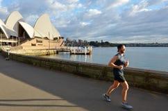 Den australiska mannen kör nära operahuset i Sydney, Australien Arkivfoton