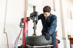 Den auto experten som använder gummihjulChangermaskinen på reparationen, shoppar royaltyfri bild