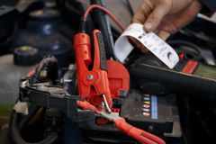 Den auto mekanikern använder multimetervoltmetern för att kontrollera spänningsnivån i bilbatteri royaltyfri fotografi