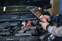 Den auto mekanikern använder multimetervoltmetern för att kontrollera spänningsnivån i bilbatteri royaltyfria foton