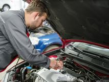 Den auto mekanikern kontrollerar bilen under huven royaltyfria foton