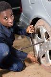 Den auto mekanikern tar bort gummihjulet från en bil arkivbild