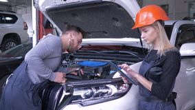 Den automatiska reparationen shoppar, tekniker man och kvinnabruksminnestavlan, medan reparera bilen med den öppna huven och medd stock video