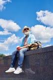 Den avkopplade grabben åldrades av tyckande om stad 50-60, medan dricka kaffe Royaltyfri Fotografi