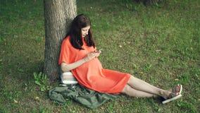 Den avkopplade gravida flickan använder smartphonen som sammanträde för den rörande skärmen på gräs parkerar in på varm sommardag stock video