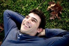 Den avkopplade mannen som in skrattar, parkerar att lägga på gräset Royaltyfri Fotografi