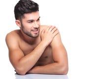 Den avkopplade nakna mannen är le och se till hans sida Royaltyfri Bild