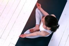Den avkopplade unga kvinnan i yogameditation poserar inomhus royaltyfria foton