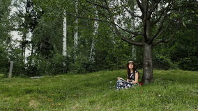Den avkopplade unga kvinnan läser en bok under trädskuggan under sommarsemester på bygden lager videofilmer