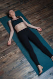 Den avkopplade unga kvinnan som ligger på yogameditation, poserar Royaltyfri Bild