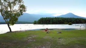 Den avlägsna siktsflickan ändrar yoga poserar på sjöbanken lager videofilmer