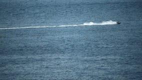 Den avlägsna strålen skidar ryttaren på havet, ultrarapidvideo arkivfilmer