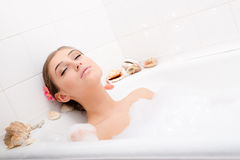 Den avslappnande attraktiva sexiga unga kvinnan som ligger i badet med skum som tycker om ögon för brunnsortavkopplingbehandling, Arkivbilder