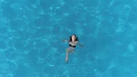 Den avslappnande flickan svävar i pöl med kristallklart vatten och att tycka om sommarferier, flyg- sikt arkivfilmer