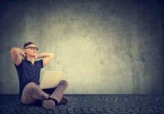 Den avslappnande mannen med bärbar datorsammanträde med ögon stängde sig arkivfoton