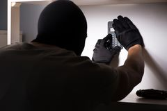 Den bärande balaclavamaskeringen för inbrottstjuv på brottsplatsen royaltyfri bild