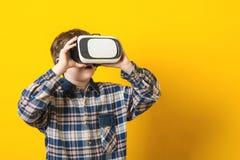 Den bärande virtuella verkligheten för pojken rullar med ögonen över gul bakgrund Royaltyfri Fotografi