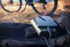 Den bärbara uppladdaren laddar smartphonen Maktbank med kabel mot bakgrunden av cykeln arkivbild