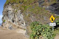 Den bärnstensfärgade klippan faller det varnande tecknet Arkivbild