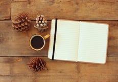 Den bästa bilden av den öppna anteckningsboken med tomma sidor, bredvid sörjer kottar och koppen kaffe över trätabellen retro fil Arkivfoto