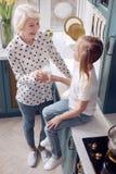 Den bästa sikten av äldre ge sig för kvinna mjölkar till hennes sondotter Royaltyfria Bilder
