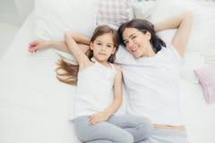 Den bästa sikten av att älska den unga modern med angenäma leendelögner nära hennes lilla dotter som går att ha sömn, tycker om l royaltyfri fotografi