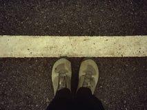 Den bästa sikten av att fotvandra startar från över, fot för en person, i att fotvandra kängor som står på gränslinjen Arkivbilder