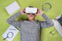 Den bästa sikten av bärande virtuell verklighet för den asiatiska mannen rullar med ögonen Ligga för man Royaltyfria Bilder