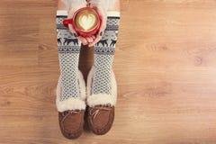 Den bästa sikten av bärbara datorn i flicka` s räcker sammanträde på ett trägolv med koppen kaffe, julgarnering, gåvor och inpack arkivfoton