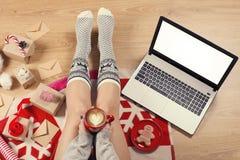 Den bästa sikten av bärbara datorn i flicka` s räcker sammanträde på ett trägolv med koppen kaffe, julgarnering, gåvor och inpack royaltyfri fotografi