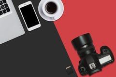 Den bästa sikten av bärbara datorn, ilar telefonen, bildkortet, kameran och koppen kaffe som ligger på röd och svart yttersida Ar Royaltyfri Foto