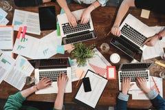 Den bästa sikten av barn som coworking folk, arbetar på bärbara datorer och pappers- dokument Grupp av högskolestudenter som anvä royaltyfri foto