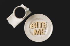 Den bästa sikten av bokstäver biter mig gjorde från kakadeg på plattan med kaffekoppen Royaltyfri Bild