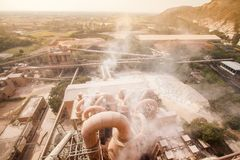 Den bästa sikten av cementfabriken, dammigt och ånga blåste i fabriken, byn och berget i dammet i aftonen som var varm arkivfoto