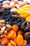Den bästa sikten av den centrala asiatet torkade frukter och muttrar i en typisk blå keramisk platta Torkade aprikors, mango, fik Arkivbild
