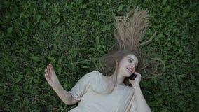 Den bästa sikten av damen som ligger på grönt gräs och talar på mobil eller, ilar telefonen arkivfilmer