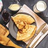 Den bästa sikten av de ryska maträttpannkakorna, mjölkar, sitter fast, den vita choklad, handduken, potholderen, kniven och gaffe arkivbild