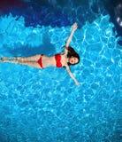 Den bästa sikten av den sexiga bikinin för mode garvade modellen i swimm för blått vatten royaltyfria foton