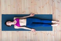 Den bästa sikten av den unga kvinnan som ligger i lik, eller liket poserar att koppla av efter praktiserande yoga Fotografering för Bildbyråer