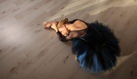 Den bästa sikten av den yrkesmässiga ballerina i blåa ballerinakjol- och pointeskor sitter och sträcka på golv Copyspace Arkivfoto