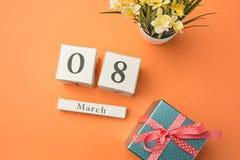 Den bästa sikten av det orange skrivbordet med gåvan, blommor och anteckningsboken Fotografering för Bildbyråer
