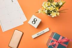 Den bästa sikten av det orange skrivbordet med telefonen, gåvan, blommor och anteckningsboken Arkivbild