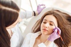 Den bästa sikten av en kvinna en klient ligger på tillvägagångssättet för ögonbrynkorrigering arkivbild