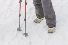 Den bästa sikten av fot i kängor och damasker snöar skydd i snoen Royaltyfri Foto