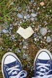 Den bästa sikten av hjärta formade den vita stenen och gymnastikskor royaltyfria bilder