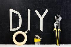 Den bästa sikten av den justerbara skiftnyckeln, klibbigt band, förhäxer tangenten och ordet DIY Royaltyfria Bilder