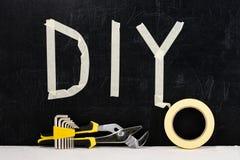 Den bästa sikten av den justerbara skiftnyckeln, klibbigt band, förhäxer tangenten och ordet DIY Fotografering för Bildbyråer